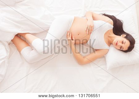 Top view of pretty young pregnant woman is sleeping on bed. She is lying and touching her abdomen gently