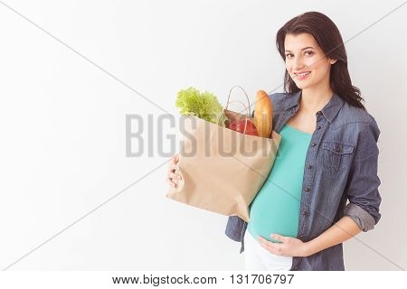 Portrait of beautiful young pregnant woman holding a packet of healthy food. She is standing and smiling. The lady is touching her belly gently. Isolated and copy space in left side