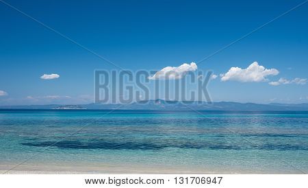 View from a beach across a clear blue sea