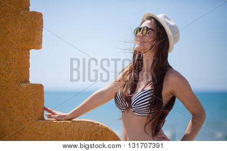 Woman In Hat On Beach Near The Sea During Summer Vacation
