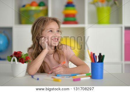 Cute little student girl at art class at school