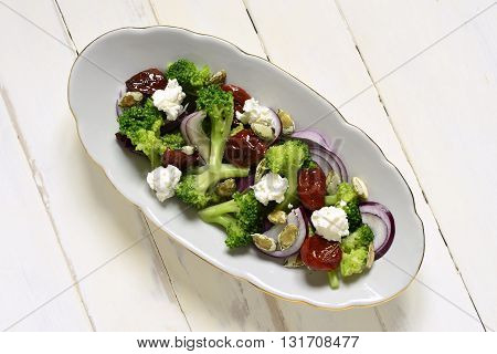 Salad with broccoli dried tomatoes feta onions and pumpkin seeds, top view