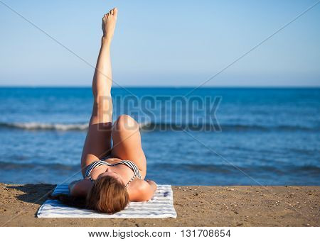 Woman On The Beach During Summer Vacation Enjoying Hot Sun