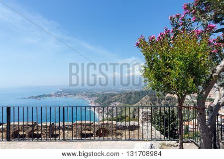 Panorama Taormina and Mediterranean Sea with southward view at a smoking Etna volcano Sicily Italy