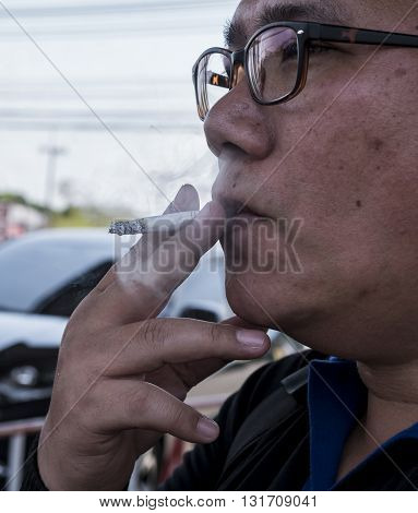 Portrait of single man hold cigar by hand and smoking cigarette on the street in the afternoon