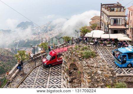 CASTELMOLA ITALY - MAY 19: Panorama of Castelmola town square with tourists buses and an aerial view at Taormina covered with raining clouds on May 19 2016 in Castelmola at the island Sicily Italy