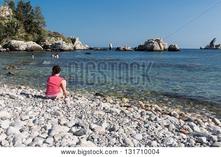 TAORMINA ITALY - MAY 21: Lonely tourist making a phone call at the beach of Taormina on May 21 2016 at the island Sicily Italy