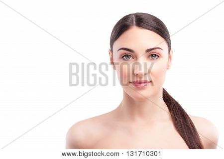 Portrait of attractive young woman caring of her skin. She is standing and looking at camera with joy. Isolated and copy space in left side
