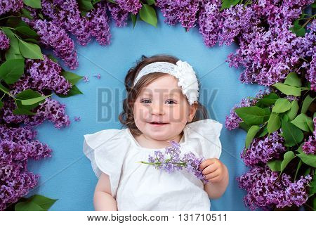 pretty little baby girl lying on blue background with lilac flowers