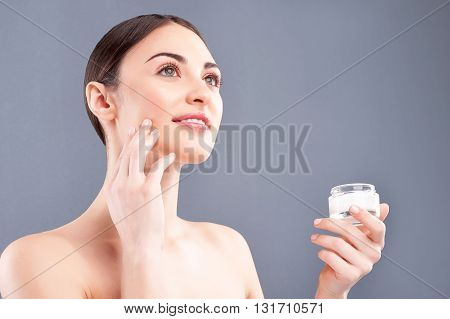 Portrait of attractive healthy girl applying cream on her face. She is standing and looking forward pensively. The lady is smiling. Isolated on grey background