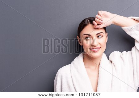Portrait of pretty young girl relaxing in bathrobe. She is standing and raising arm to face. The lady is smiling. Isolated and copy space in left side