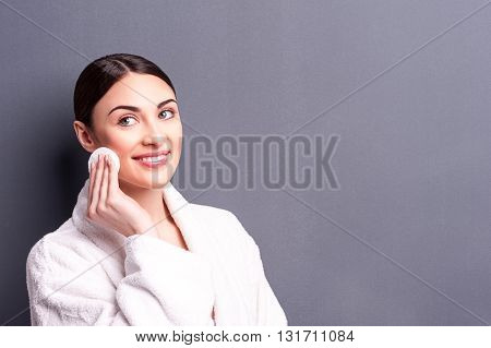 Portrait of cheerful young woman touching her face with a sponge. She is standing in bathrobe and smiling. Isolated and copy space in right side