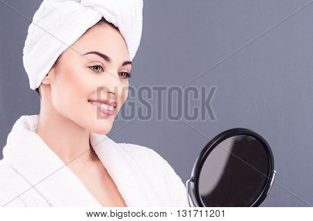 Waist up portrait of beautiful healthy girl looking at the mirror with satisfaction. She is standing and smiling. The lady is wearing bathrobe and towel on head. Isolated