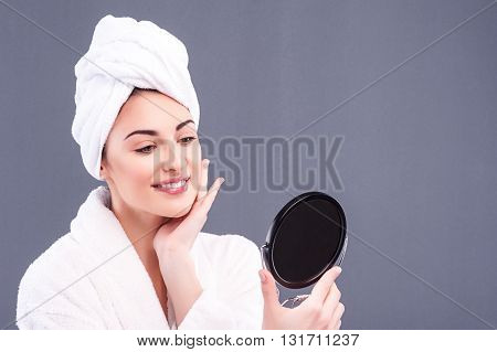 Beautiful healthy girl is touching skin on her face gently. She is standing and looking at mirror with satisfaction. The lady is smiling. Isolated and copy space in right side