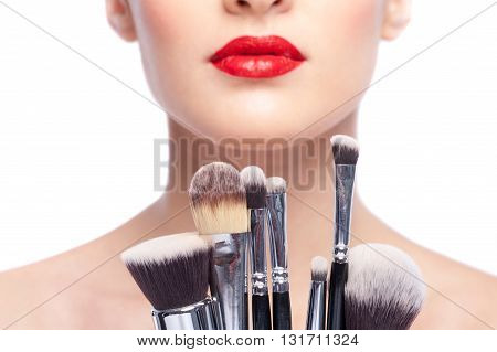 Close up of set of make-up brush near female face. Beautiful girl has bright red lips. Isolated