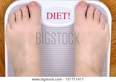 Barefoot person standing on the weight scale. The scale shows DIET!