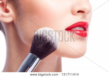 Close up of powder brush applying powder of female cheek. Young woman has red lips. Isolated