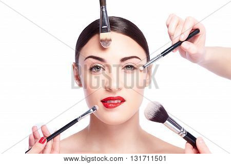 Team of beauticians are applying powder and eyeshadows on female face. Sexy woman is biting red lips and looking forward with passion. Isolated