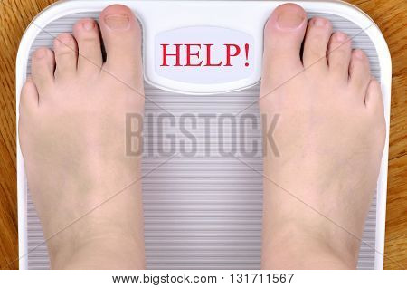 Barefoot person standing on the weight scale. The scale shows HELP!