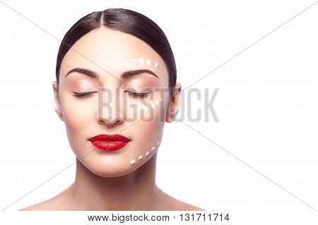 Portrait of attractive young woman standing and relaxing. She has cream on her face. Her eyes are closed with pleasure. Isolated and copy space in right side
