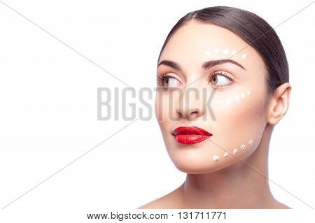 Portrait of attractive young woman caring of her skin. She is standing with cream on her face. The lady is looking aside with confidence. Isolated and copy space in left side