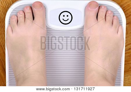 Barefoot person standing on the weight scale. The scale shows smiley face