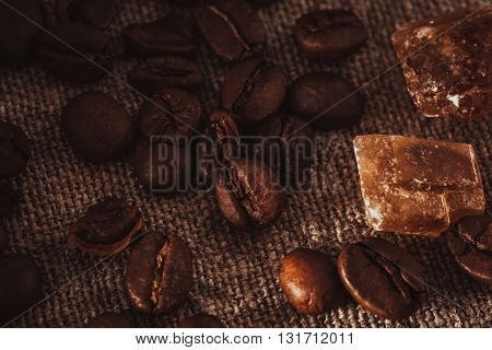 scattering of coffee beans and dark candy sugar on textile