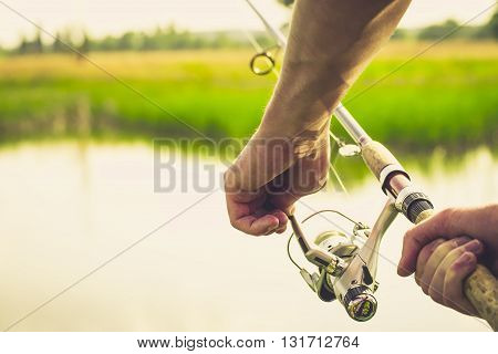 Fisherman start to fishing by spinning on river in sunny weather