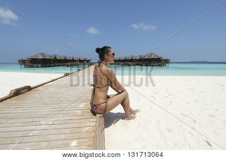 girl in bikini on the shore near the water bungalows in the Maldives resort
