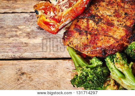 Grilled meat, mushrooms, broccoli and bell pepper on the wooden table