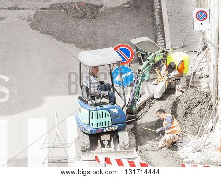 Udine , Italy - May 2 2016 : Sidewalk under construction curb and gutter installation in progress Construction workers.
