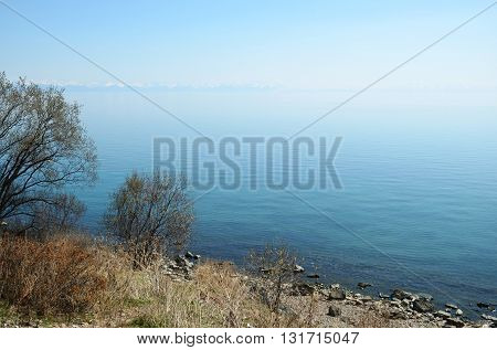 The smooth calm surface of Lake Baikal in spring. Listvyanka village