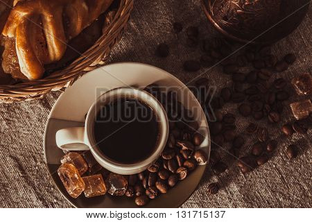A cup of coffee on textile with coffee beans, dark candy sugar, pots, basket and cake