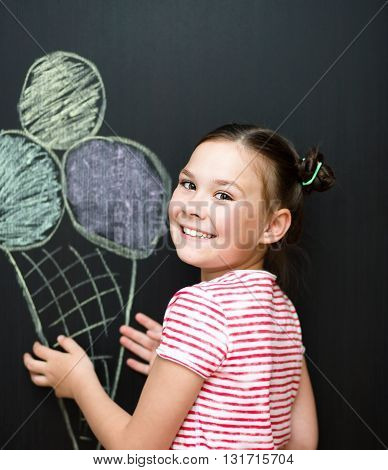 Cute happy girl is eating ice-cream. On a black background