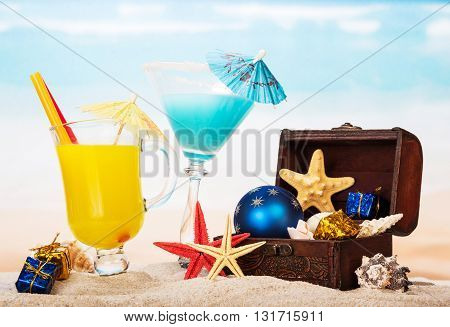 Cocktail, orange juice, starfish, treasure chest with Christmas ball and gifts in the sand against the sea.