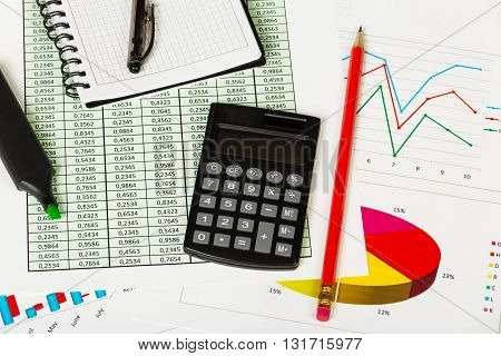 Notepad, pen, marker, pencil and calculator on the background of graphs.