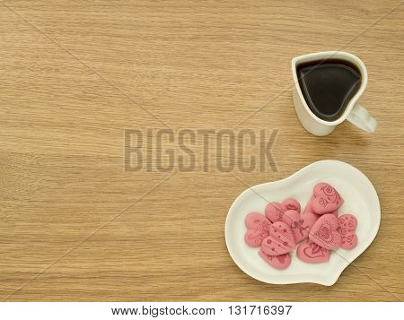 Heart shape of cup with coffee and heart shape of plate with pink sweet hearts in white plate. Love coffee. Top view. Happy Valentines Day background.