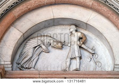 LUCCA, ITALY - JUNE 06, 2015: The right portal of the Cathedral of St Martin in Lucca. Lunette depicts the Beheading of Saint Regulus, Lucca, Italy, on June 06, 2015