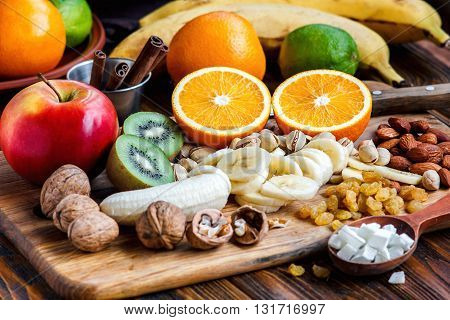 Fresh fruits. Healthy food. Mixed fruits and nuts background.Healthy eating, dieting, love fruits. Studio photography of different fruits and nuts on old wooden table. Organic Healthy Assorted Fruits.