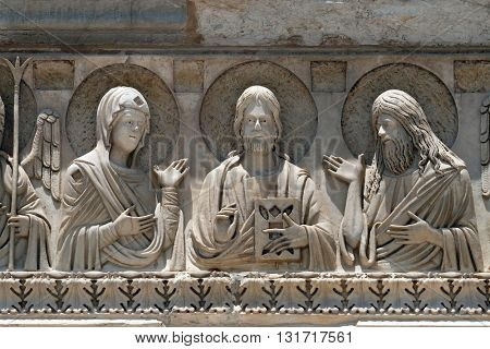 PISA, ITALY - JUNE 06, 2015: Virgin Mary, Jesus and St. John the Baptist, Baptistery decoration architrave arches, Cathedral in Pisa, Italy. Unesco World Heritage Site, on June 06, 2015