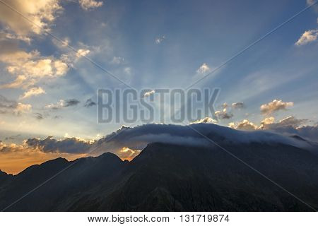 Rays of light shining through dark clouds over the mountains