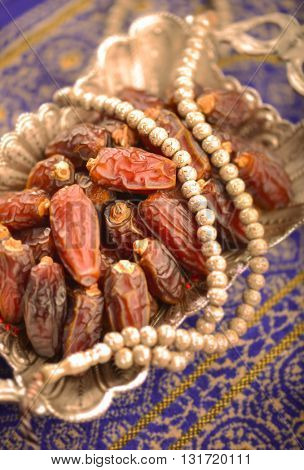 Close up of good arabic quality dates and rosary - table top photography