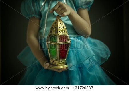 A Close up of a girl holding beautiful decorative Ramadan lantern in hand. Celebration in Holy month of  Ramadan.