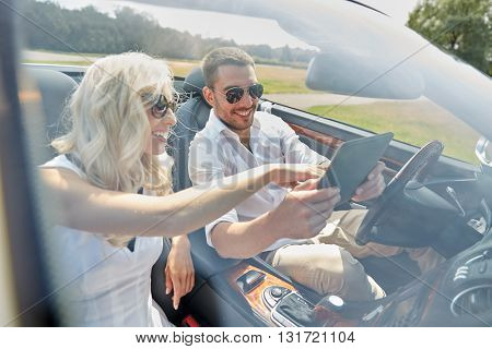 road trip, travel, summer vacation, technology and people concept - happy couple with tablet pc in cabriolet car