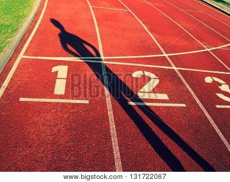 Athlete dark sharp body shadow on a red running track in stadium