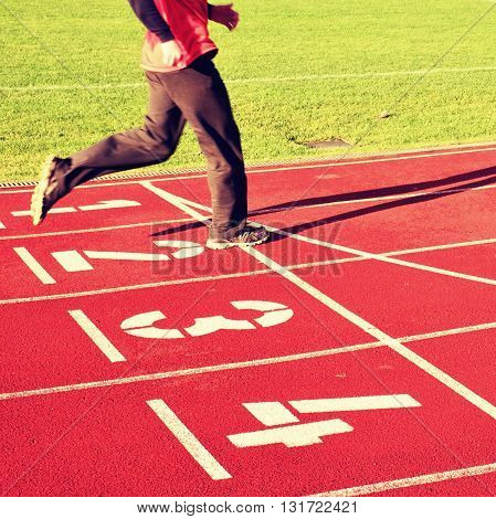 Red Running Racetrack On The Stadium With Two Running Legs In Tracksuit Trousers