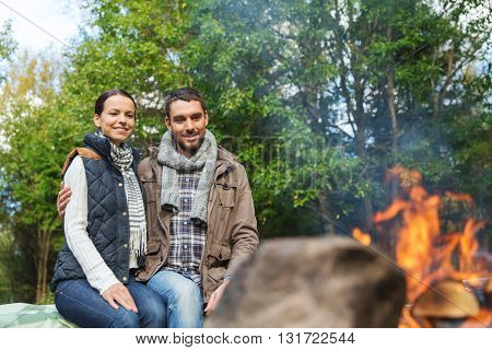 camping, travel, tourism, hike and people concept - happy couple sitting on bench and warming near campfire at camp in woods