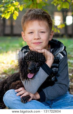 Boy sitting with a black poodle in an embrace on the nature