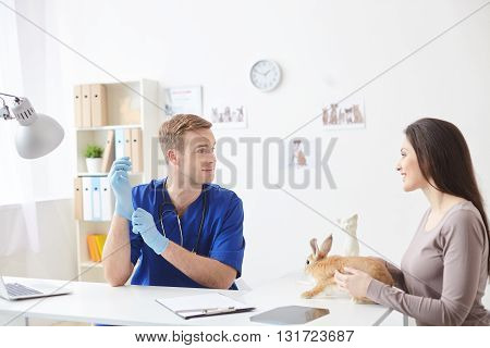 Beautiful young woman is showing her small rabbit to the doctor. She is holding an animal and smiling. The man is sitting at desk and wearing gloves
