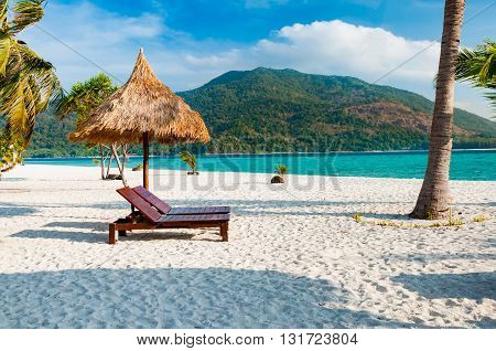 Empty wooden beach chairs with parasol on the beach with coconut tree in Phuket Thailand with parasol on the beach with coconut tree in Phuket Thailand
